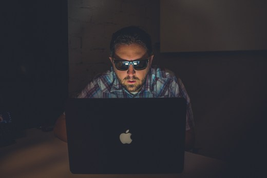 Man with sunglasses looking at Apple laptop screen in the dark