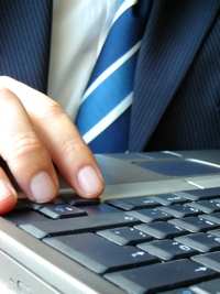 Man in business suit typing on laptop keyboard